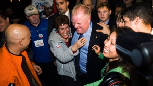 In this Monday, Oct. 25, 2010 photo, Toronto Mayor-elect Rob Ford, center, is greeted by a mob of supporters as he arrives to speak to supporters in Toronto. AP / The Canadian Press, Nathan Denette)