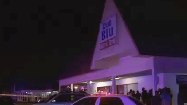 In this frame from video, people gather near the scene of a fatal shooting at Club Blu nightclub in Fort Myers, Fla., on July 25, 2016. (WBBH via AP)
