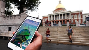"""In this Monday, July 18, 2016, photo, a """"Pokemon Go"""" player shows his mobile phone while walking through the Boston Common, outside the Massachusetts Statehouse in Boston. Historical markers dot the landscape of old cities, barely noticed by passers-by. (AP / Charles Krupa)"""