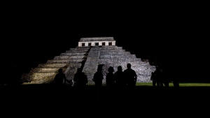 Journalists appear silhouetted against a Mayan temple, in Palenque, Mexico, on March 10, 2008. (AP Photo/Alexandre Meneghini)