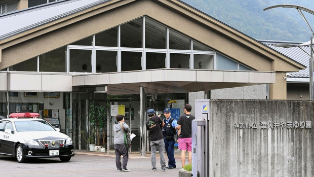 A police officer talks with visitors in front of a facility for the handicapped where a number of people were killed and dozens injured in a knife attack Tuesday, July 26, 2016, in Sagamihara, outside Tokyo. (Kyodo News via AP)