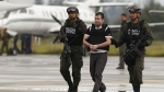 Daniel Barrera, centre, is escorted by police to a waiting car prior to his extradition to the U.S. from the counter-narcotics base in Bogota, Colombia on Tuesday July 9, 2013. (AP / Fernando Vergara)