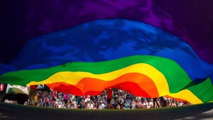 A large rainbow flag is carried down Robson Street during the Vancouver Pride Parade in Vancouver, B.C., on Sunday, August 2, 2015. THE CANADIAN PRESS/Darryl Dyck