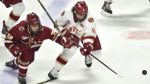 Denver's Trevor Moore (8), right, and Boston College's Austin Cangelosi (26) fight for control of the puck during the second period of the regional semifinal in the NCAA college hockey tournament Saturday, March 28, 2015, in Providence, R.I. (AP / Gretchen Ertl)