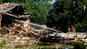 Firefighters spray water after an explosion levelled a house in Omaha, Neb. on Monday, July 25, 2016. (Chris Machian / Omaha World-Herald)