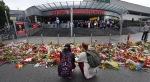 Flowers and candles have been placed in front of the main entrance of the Olympia-Einkaufszentrum (Olympia Shopping Mall) in Munich, Germany, Monday, July 25, 2016, after a rampage that left numerous people dead and injured. (Peter Kneffel / dpa via AP)