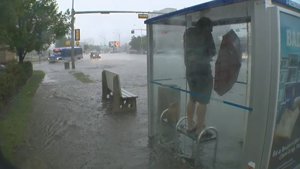 A transit user stands on a bench in a bus shelter on 104 Ave. on Wednesday, July 27, as a powerful storm pounded Edmonton.