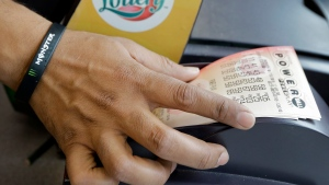 In this Jan. 13, 2016 file photo, a clerk at a convenience store pulls Powerball tickets from a printer for a customer in Tampa, Fla. (AP Photo/Chris O'Meara, File)