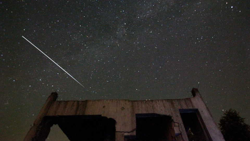 Stars and meteor streaks are seen behind a destroyed house, near Tuzla, Bosnia, Wednesday, Aug. 12, 2015 during the Perseid meteor shower. (AP Photo / Amel Emric)