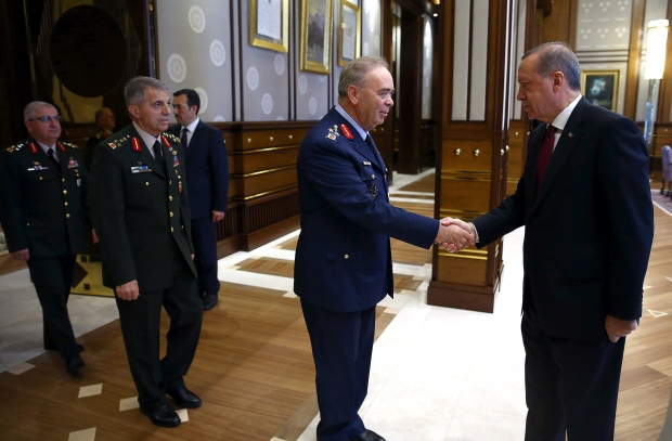 Turkey President Recep Tayyip Erdogan, right, shakes hands with the Commander of Turkish Air Forces General Abidin Una during a meeting with the top-level military chiefs at the Presidential palace in Ankara, Turkey, on Friday, July 29, 2016. (Kayhan Ozer / Presidential Press Service)