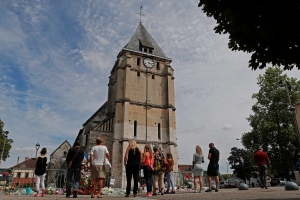 Residents pay tribute at a makeshift memorial in front of the Saint Etienne church where Priest Jacques Hamel was killed on 26 July in a hostage taking in Saint-Etienne-du-Rouvray, Normandy, France, Thursday, July 28, 2016. (AP / Francois Mori)