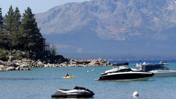 In this Aug. 24, 2015 file photo, a kayaker paddles in Lake Tahoe, Nev. A new study says the average surface temperature of Lake Tahoe has risen faster over the last four years than any time on record - 15 times faster than the long-term warming rate over the past half century. (Rich Pedroncelli, File/AP Photo)