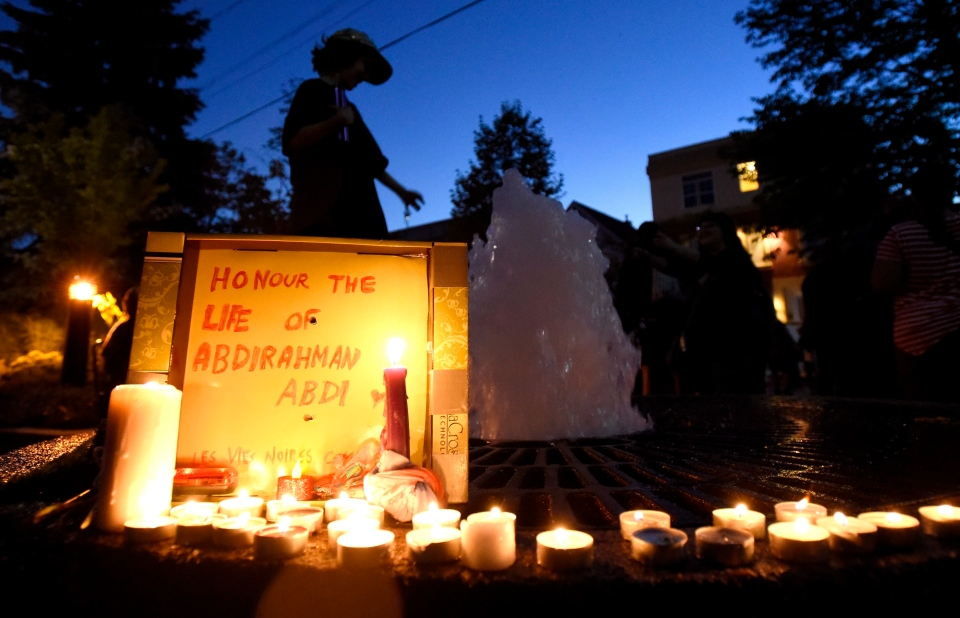 A boy plays in a fountain surrounded by candles lit in a memorial for Abdirahman Abdi, who died after an altercation with Ottawa Police officers Sunday, on Tuesday, July 26, 2016 in Ottawa. (THE CANADIAN PRESS/Justin Tang)