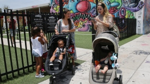 Vanessa Gomez, 33, left, with her son Ezra, 2, and her friend Cristy Fernandez, 33, with her 9-month-old- son River, of Miami, walk in the Wynwood neighborhood of Miami, Friday, July 29, 2016. (AP Photo / Marta Lavandier)