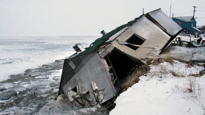 In this Dec. 8, 2006, file photo, Nathan Weyiouanna's abandoned house at the west end of Shishmaref, Alaska, sits on the beach after sliding off during a fall storm in 2005. (AP Photo / Diana Haecker, File)
