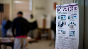 This photo taken March 15, 2016, shows a North Carolina Voter ID rules posted at the door of the voting station at the Alamance Fire Station in Greensboro, N.C. (Andrew Krech/News & Record via AP)