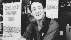 In this Nov. 9, 1977 photo, Harvey Milk poses in front of his camera shop in San Francisco. (AP Photo/File)