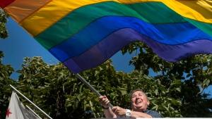 Marci Burba waves a rainbow flag at the Sacramento LGBT Community Center in Sacramento, Calif., on Friday, June 26, 2015. (Randall Benton / The Sacramento Bee via AP)