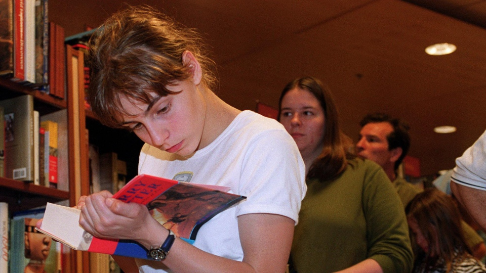 In this file photo, Hermina Munro, 15, is fully engrossed in 'Harry Potter and the Goblet of Fire' as she stands in line to pay for it at book store in Toronto on Saturday July 8, 2000. (CP PHOTO / Tannis Toohey)