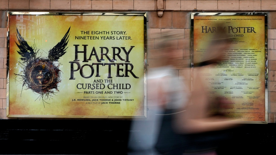 In this photo taken on Thursday, July 28, 2016, pedestrians pass a poster advertising the new Harry Potter play, at the Palace Theatre in London. (AP Photo / Kirsty Wigglesworth)