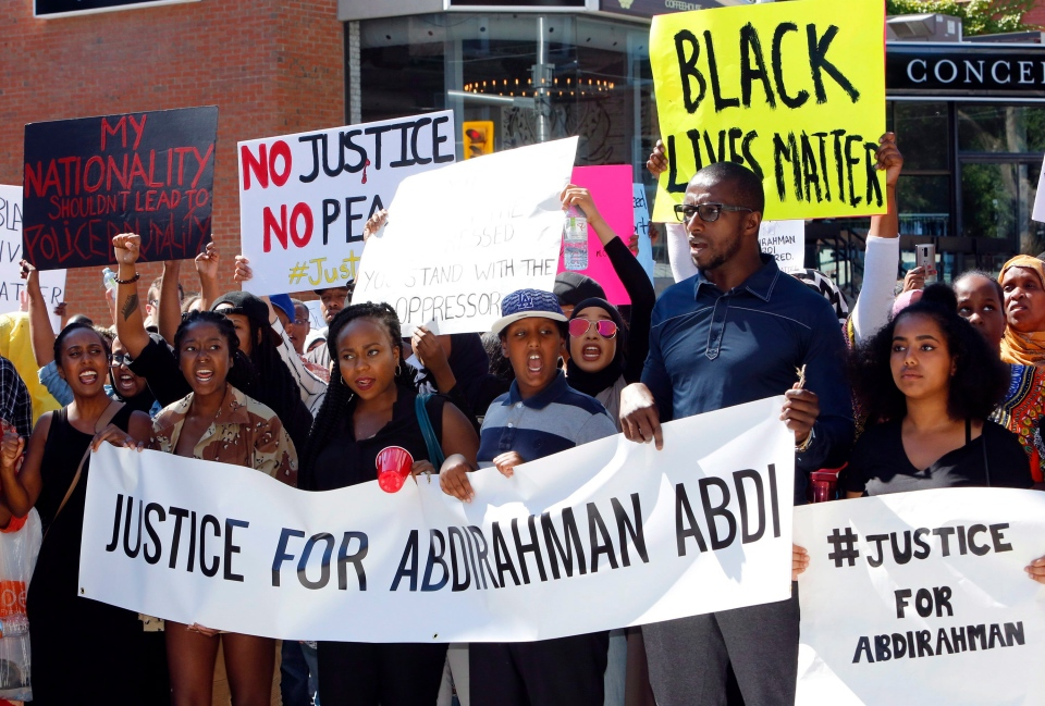 People assemble to honour Abdirahman Abdi in a protest at Ottawa's police headquarters on Saturday, July 30, 2016. Abdi, 37, died following a confrontation with police last Sunday in front of his home in downtown Ottawa. (Fred Chartrand / THE CANADIAN PRESS)
