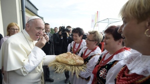 Pope Francis tastes the bread we was offered by women wearing Polish traditional clothes during his visit at a Caritas charity organization house, in Krakow, Poland, Sunday, July 31, 2016. (L'Osservatore Romano / Pool Photo via AP)