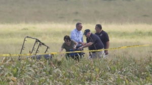 The partial frame of a hot air balloon is visible above a crop field as investigators comb the wreckage of a crash Saturday, July 30, 2016, in Central Texas near Lockhart, Texas. (Ralph Barrera / Austin American-Statesman via AP)
