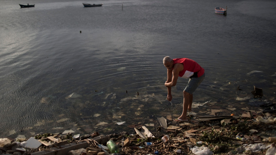 A man washes himself in the polluted waters of Guanabara Bay in Rio de Janeiro, Brazil, Saturday, July 30, 2016. (AP / Felipe Dana)