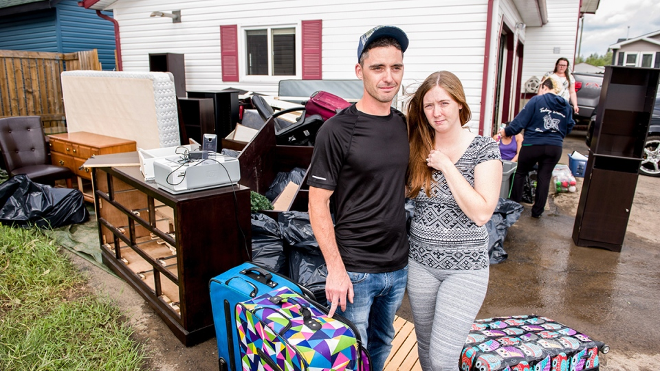Homeowners Kenny and Kayla Payne pose beside the wet contents of their basement in the Gregoire neighborhood of Fort McMurray, Alta., on Monday, Aug. 1, 2016. (Greg Halinda / THE CANADIAN PRESS)