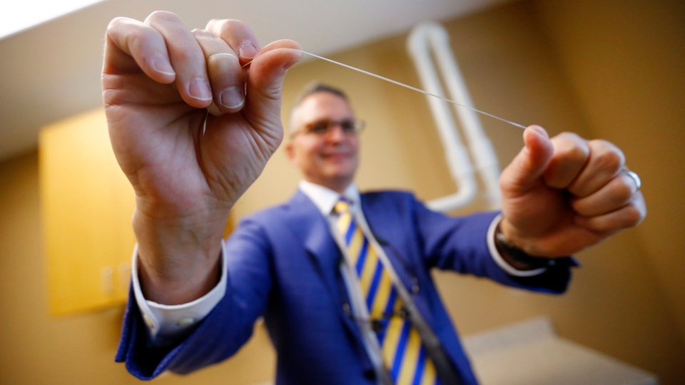 Dr. Wayne Aldredge, president of the American Academy of Periodontology, holds a piece of dental floss at his office in Holmdel, N.J. (AP / Julio Cortez)
