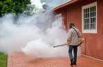 A Miami-Dade County mosquito control worker sprays around a home in the Wynwood area of Miami on Monday, Aug. 1, 2016. The CDC has issued a new advisory that says pregnant women should not travel a Zika-stricken part of Miami, and pregnant women who live there should take steps to prevent mosquito bites and sexual spread of the virus. (AP Photo/Alan Diaz)
