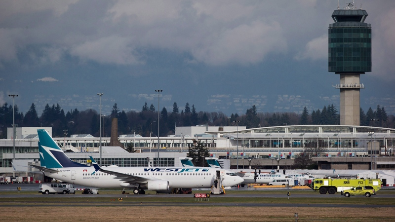 A Westjet Boeing 737-800 aircraft sits parked on the south runway after aborting a takeoff due to a blown tire at Vancouver International Airport in Richmond, B.C., on Monday, Feb. 1, 2016. (Darryl Dyck / THE CANADIAN PRESS)
