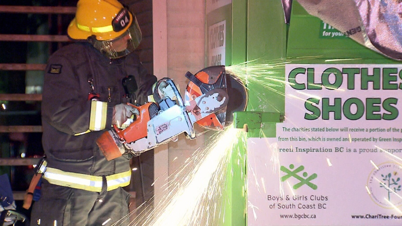 A firefighter cuts through the door of a clothing donation bin in Vancouver on Thursday, Aug. 4, 2016.