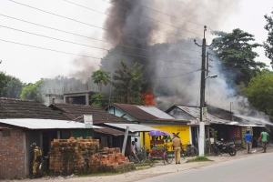 A fire burns after rebels opened fire in a crowded market at Kokrajhar, in the north-eastern Indian state of Assam, India, Friday, Aug. 5, 2016. (AP Photo)