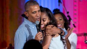 "FILE - President Barack Obama hugs and sings ""Happy Birthday"" to his daughter Malia Obama on stage during an Independence Day celebration in the East Room of the White House, in Washington, Monday, July 4, 2016. (AP Photo/Carolyn Kaster)"