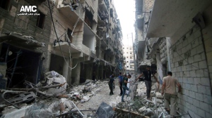 In this Friday, July. 29, 2016 file photo, Syrian citizens inspect damaged buildings after airstrikes hit Aleppo, Syria. (Aleppo Media Center via AP)