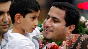 In this July 15, 2010 file photo, Shahram Amiri, an Iranian nuclear scientist greets his son Amir Hossein as he arrives to the Imam Khomeini airport after returning from the United States, outside Tehran, Iran. Amiri, who was caught up in a real-life U.S. spy mystery and later returned to his homeland and disappeared, has reportedly been executed under similarly mysterious circumstances. Amiri was reportedly hanged this week and family members held a memorial service for him in the Iranian city of in Kermanshah, 500 kilometers (310 miles) southwest of Tehran. State media in Iran, which has been silent about Amiri's case for years, has not reported his death. (AP Photo/Vahid Salemi, File)