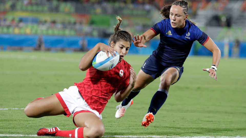 Canada's Bianca Farella, left, scores a try France's Jade le Pesq, watches on during the women's rugby sevens quarter-final match at the Summer Olympics in Rio de Janeiro, Brazil, Sunday, Aug. 7, 2016. Canada took the match 15-5. (Themba Hadebe/THE ASSOCIATED PRESS)