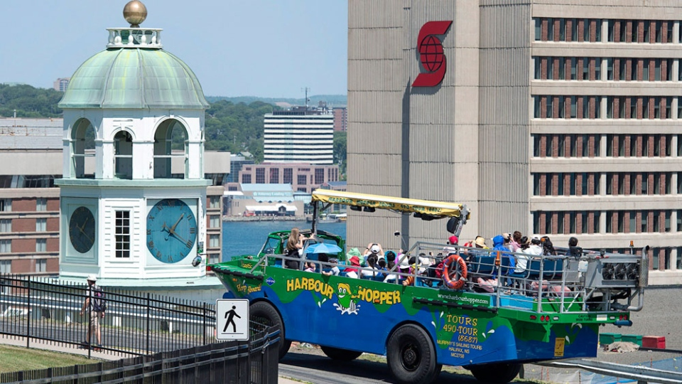 The Harbour Hopper carries a load of tourists past the Old Town Clock on Citadel Hill in Halifax on Friday, Aug. 5, 2016. The Vietnam war-era amphibious vehicle also provides a water view of the Nova Scotia capital city. (THE CANADIAN PRESS/Andrew Vaughan)