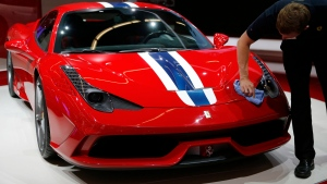 FILE - In this Sept. 11, 2013, file photo, a man cleans a Ferrari 458 Speciale at the 65th Frankfurt Auto Show in Frankfurt, Germany. (AP Photo/Frank Augstein, File)
