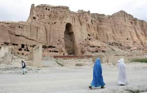 In this June 17, 2009 file photo, two women walk past the cliffs that once held giant Buddhas destroyed by the Taliban in 2001 in Bamiyan, central Afghanistan. (AP Photo/Rahmat Gul, File)