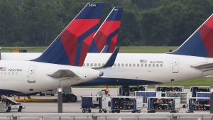 Luggage and Delta planes on the tarmac at Orlando International Airport on Aug. 8, 2016. (Red Huber / Orlando Sentinel via AP)