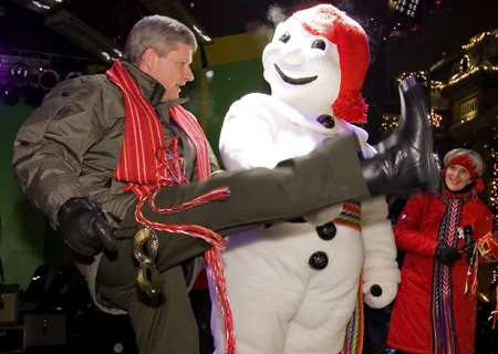 Prime Minister Stephen Harper dances as Bonhomme Carnaval looks on at the official opening of the Quebec Carnival Friday, Jan. 30, 2009 in Quebec city. (THE CANADIAN PRESS / Clement Allard)