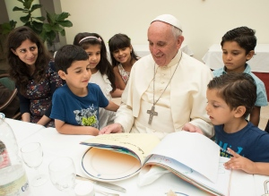 Pope Francis smiles as he browses through drawings at the Vatican, Thursday, Aug. 11, 2016. Pope Francis has had lunch with a group of Syrian refugees who were brought to Italy from the Greek island of Lesbos thanks to the pope's intercession. (L'Osservatore Romano/Pool Photo via AP)