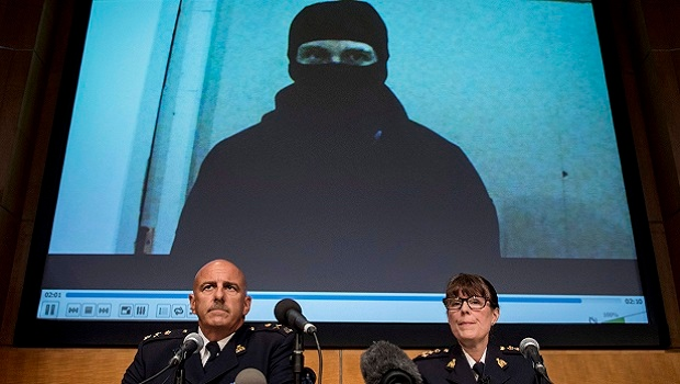 Video footage showing Aaron Driver is seen behind RCMP Deputy Commissioner Mike Cabana (left) and Assistant Commissioner Jennifer Strachan during a press conference for what the RCMP are calling a terrorism incident, in Strathroy, Ontario yesterday, on Thursday, Aug. 11, 2016 in Ottawa. (THE CANADIAN PRESS/Justin Tang)