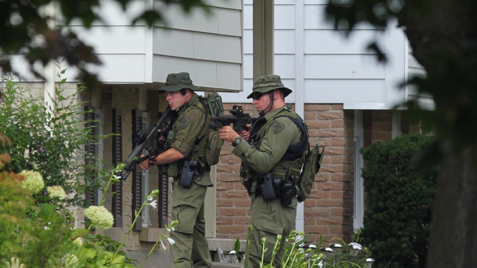 Police maintain a watch outside of a house in Strathroy, Ont., Thursday, Aug. 11, 2016. (Dave Chidley / THE CANADIAN PRESS)