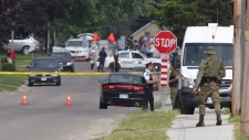 Police gather evidence outside of a house in Strathroy Ontario, Thursday, August 11, 2016. Terrorism suspect Aaron Driver was killed in a confrontation with police in the southern Ontario town of Strathroy. THE CANADIAN PRESS/ Dave Chidley