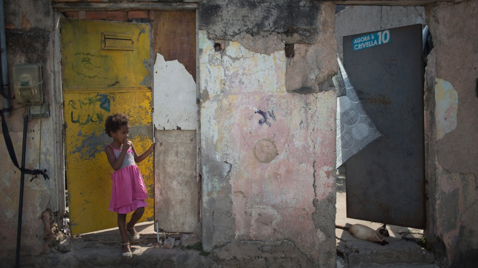 A kid stands at entrance of his house located on the same street where Brazilian judo gold medalist Rafaela Silva used to live at Cidade de Deus slum in Rio de Janeiro, Brazil, Tuesday, Aug. 9, 2016. (AP Photo/Leo Correa)