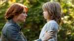This image released by Disney shows Bryce Dallas Howard, left, and Oakes Fegley in a scene from 'Pete's Dragon.' (Matt Klitscher/Disney via AP)
