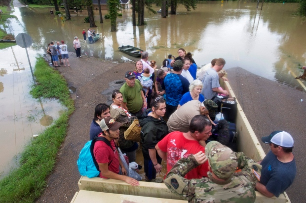 Sgt. Brad Stone of the Louisiana Army National Guard gives safety instructions to people loaded on a truck after they were stranded by rising floodwater near Walker, La., after heavy rains inundated the region, Sunday, Aug. 14, 2016. (AP Photo/Max Becherer)